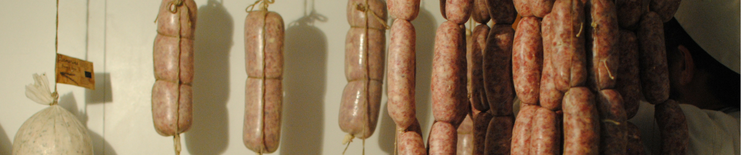 Butcher Apprentice hanging salumi at Spannocchia