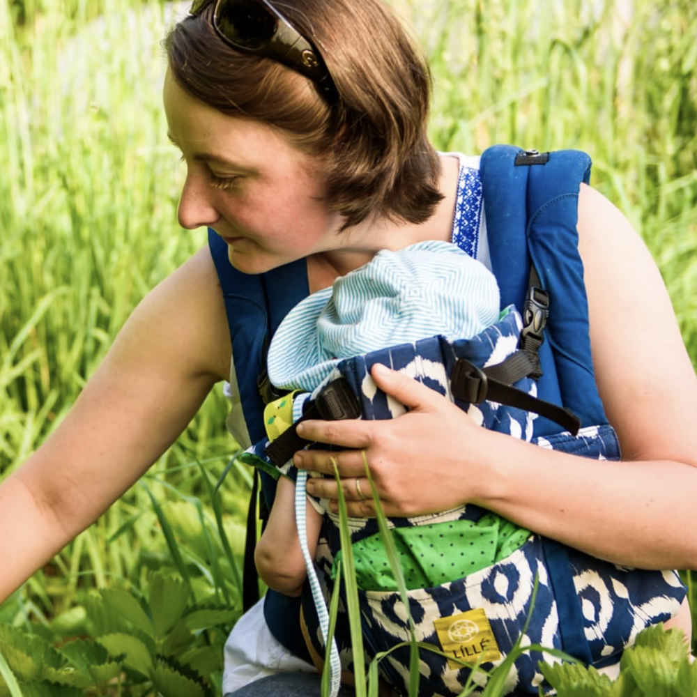 Photo of Allyson Angelini with a baby in a carrier, in a field